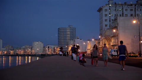 People walking in The Malecon at sunset in La Havana city in Cuba Footage