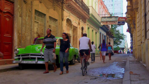 Vintage green car parked in the Habana Vieja district with people walking around Footage