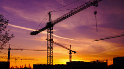 Time lapse cranes working in construction site at dusk, pan Footage