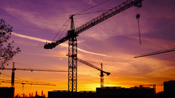 Time lapse cranes working in construction site at dusk,zoom out Footage