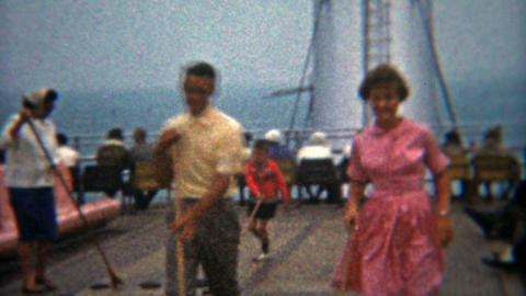 1964: Teenagers in love playing shuffleboard on a ship together Footage