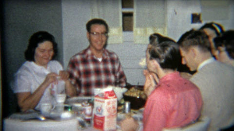 1964: Grandma cooking Thanksgiving dinner, adults and kids table Footage