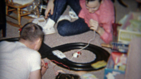 1964: Boys playing with electric car racing figure 8 crashing game Footage