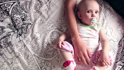 Eight month baby girl lies on the bed Live Action