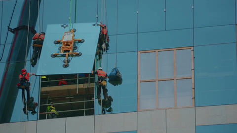 Wide shot of group of builders securing a glass panel in place Live Action