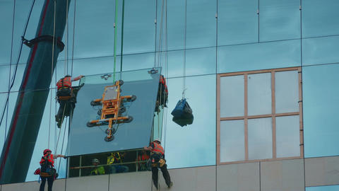 Wide timelapse shot of group of builders securing a glass panel in place Live Action