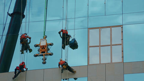 Final stage of a glass panel being secured in place by a group of builders Live Action