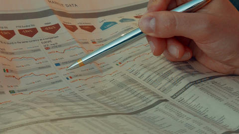 Investor Analyzing Stock Quotes In A Financial Newspaper stock footage