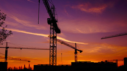 Time lapse cranes working in construction site at dusk, zoom in.Craner climbing Footage