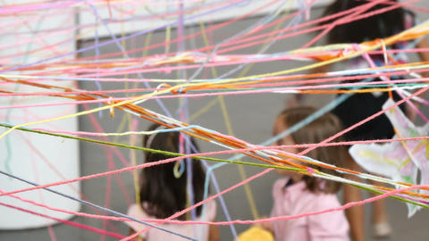 Children Playing with Skeins of Colorful Wool Footage