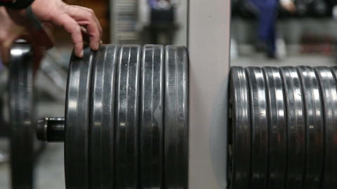 The athlete changes the weight of the load on the rod Footage