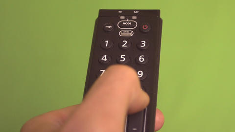 Male hand changing channels with remote control on a green screen frontal shot Footage