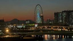 夕焼けの富士山を背景に回る観覧車と行き交う車群 Footage