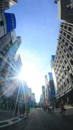 歩行者天国を歩く通行人と銀座の街並みと太陽の光芒 Footage