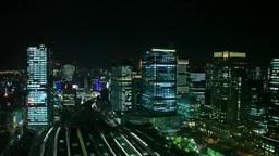 東京駅を発着する電車と丸の内と銀座などのビル群の夜景 Footage