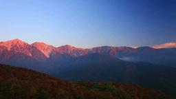 Sun Rising Over An Autumn Forest, Shiroumadake, And Hakuba Mountain Range stock footage