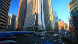 朝の新宿の高層ビル群と新都心歩道橋下交差点を行き交う Footage