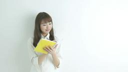 白い壁の前でノートにメモをする日本人女性 Footage