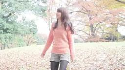 落葉の公園で笑う若い女性 Footage