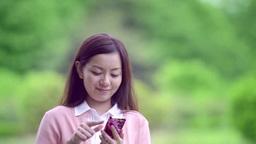 新緑とスマートフォンと女性 ภาพวิดีโอ