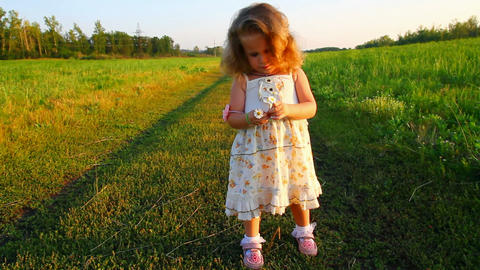 happy little girl with chamomile on meadow Stock Video Footage