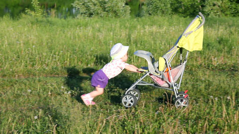 child pushes stroller on summer lawn Stock Video Footage