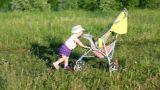 Child Pushes Stroller On Summer Lawn stock footage