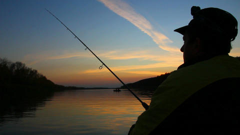 man fishes with spinning at sunset Stock Video Footage