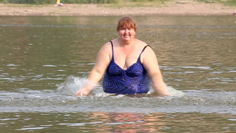 woman with overweight bath in river - slow motion Stock Video Footage