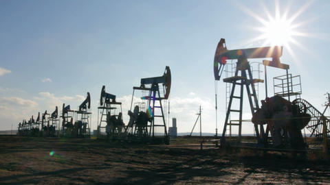working oil pumps silhouette against sun - timelap Stock Video Footage