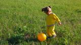 little girl playing with ball on meadow Footage