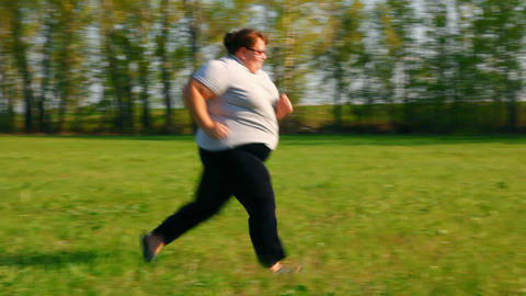 sport - overweight woman running on green meadow Stock Video Footage