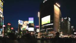 渋谷駅前のビル群の夜景と交差点を渡る人々と通過する車 Footage
