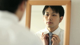 Men tying a tie while looking at the mirror Footage