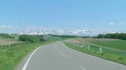 丘の道を走る車と十勝岳連邦 Footage