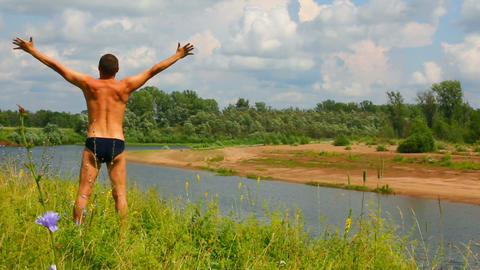 man with hands up on the river, summer Stock Video Footage