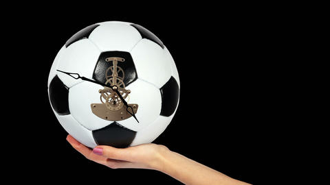 Soccer Ball Clock on the hand, on the black background, Timelapse Live Action