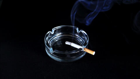 Smoldering Cigarette on the black background, Timelapse Live Action