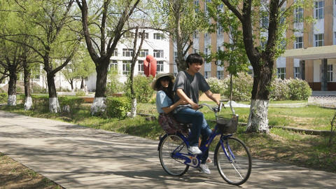 Young Chinese Couple Riding a Bicycle Stock Video Footage