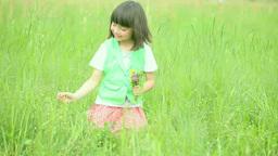 Half-Japanese girl picking flowers in a meadow Footage