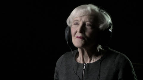 Senior woman listening to music and moving head to rhythm Stock Video Footage