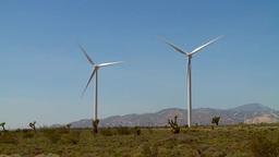 A row of wind turbines rotate on a wind farm Footage