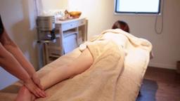 女性の左足をマッサージするセラピストの手元と後ろ姿 Footage