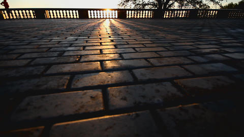 rays of sun over parapet on tile sidewalk Stock Video Footage