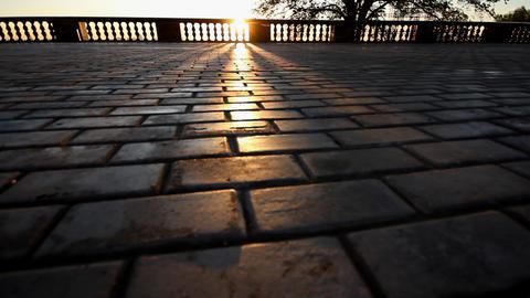 rays of sun over parapet on tile sidewalk Stock Video Footage
