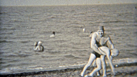 1937: Dad playing with daughter at the beach with swim caps on Footage