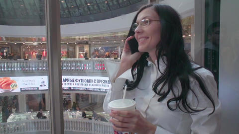 girl talking on the phone in a glass elevator to the shop Footage