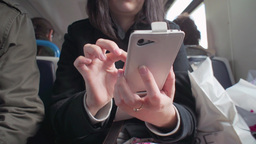 a girl with Smart Phone phone in a suburban train Footage