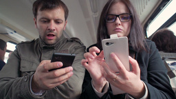 man with a girl with Smart Phone in a suburban train Footage