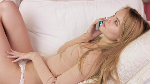 Cute girl lying on sofa with smartphone Live Action